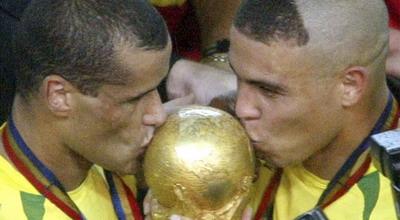 Rivaldo (kiri) sedang mencium trofi Piala Dunia 2002 bersama Ronaldo (foto:Reuterr)