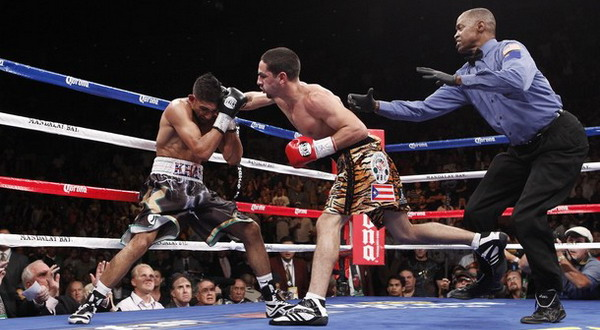 Amir Khan (kiri) terpojokan oleh pukulan Danny Garcia (kanan). Foto: Daylife