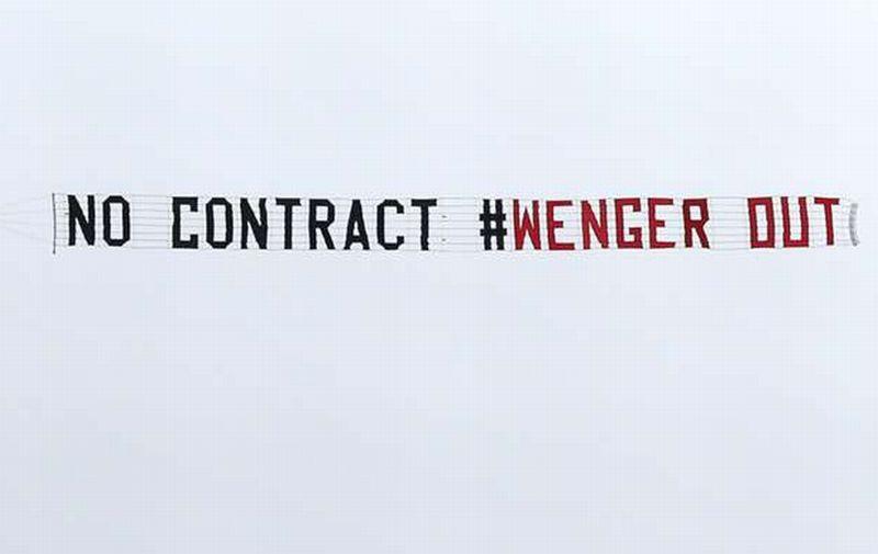 Spanduk bernada negatif untuk sang pelatih Arsenal, Arsene Wenger dengan tagar 'No Contract #WengerOut' (Foto: Getty Images)