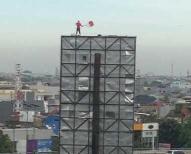 Kibarkan Merah Putih, Seorang Pria Berdiri di Atas Papan Reklame di Grogol