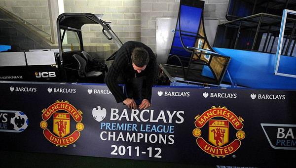 Seorang pekerja tengah mempersiapkan papan yang akan digunakan untuk selebrasi juara Manchester United/North West & Pictures Ltd