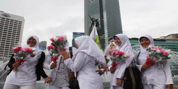 Perawat melakukan aksi damai dengan membagikan bungai di Bundaran HI (foto: Heru H/ Okezone)