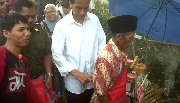 Jokowi bagikan celemek untuk pedagang kerak telor (Foto: Angkasa/Okezone)