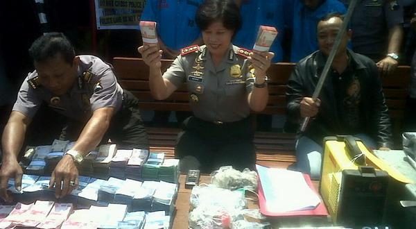 Polisi menunjukkan banrang bukti uang hasil merampok (Foto: Bramantyo/Okezone)