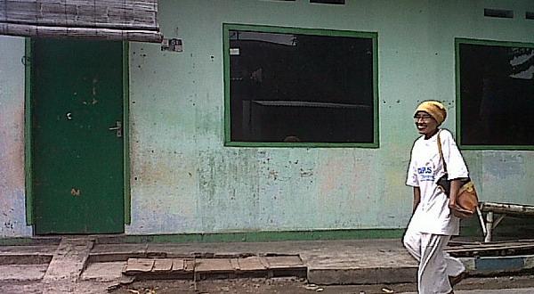 Seorang warga melintasi rumah R di Probolinggo (foto: Arie Y/Okezone)