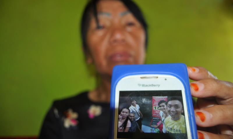 Keluarga menujukkan foto penumpang Trigana Air (foto: Antara)