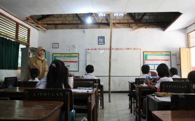 Seorang guru sedang mengajar di kelas. (Foto: Dok. Okezone)