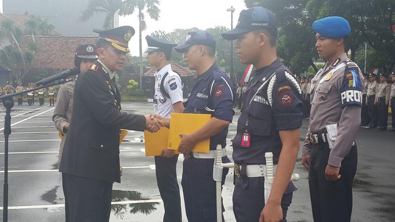 Kapolresta Tangerang Kombes Irman Sugema (kiri) menyerahkan penghargaan kepada tiga satpam yang berhasil menangkap pelaku ganjal ATM (Selly/Okezone)