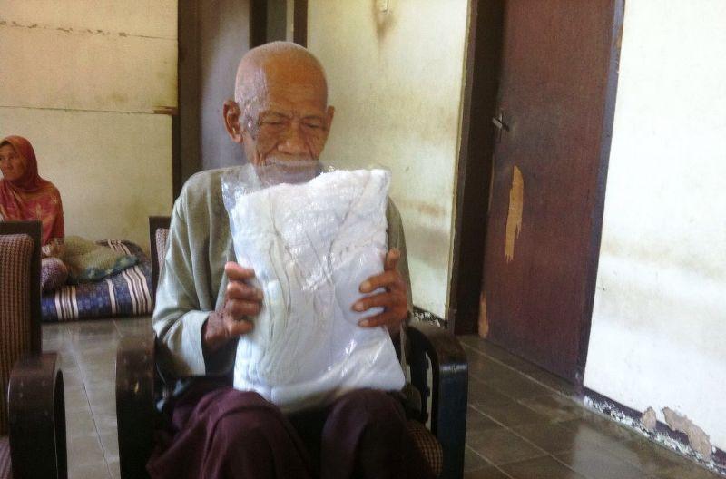 Kakek Ambari dengan bangganya memegang kain ihram untuk naik haji (Foto: Dwi Ayu/Okezone)