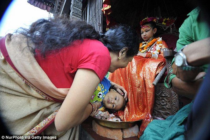 Foto seorang ibu membantu anaknya mendapatkan berkat dari Yunika (Foto: Getty Image)