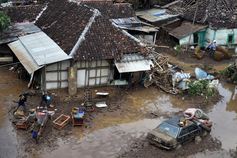 Warga mengangkut barang dari rumah yang terkena banjir bandang di aliran Sungai Ciamanuk, Tarogong Kidul, Garut, Jawa Barat (Wahyu/Antara)