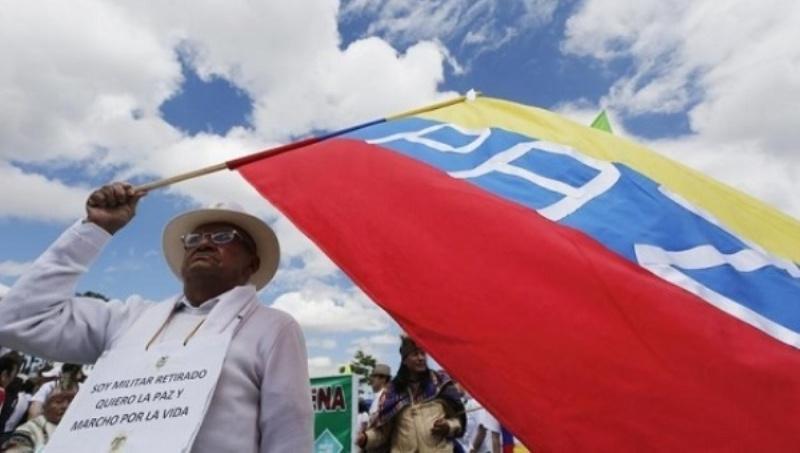 Seorang warga Kolombia mengibarkan bendera mendukung perdamaian antara pemerintah dengan FARC. (Foto: Reuters)