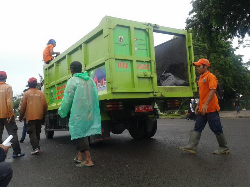Pekerja dari Dinas Kebersihan mulai memungut kantong sampah. (Fahreza R/Okezone)