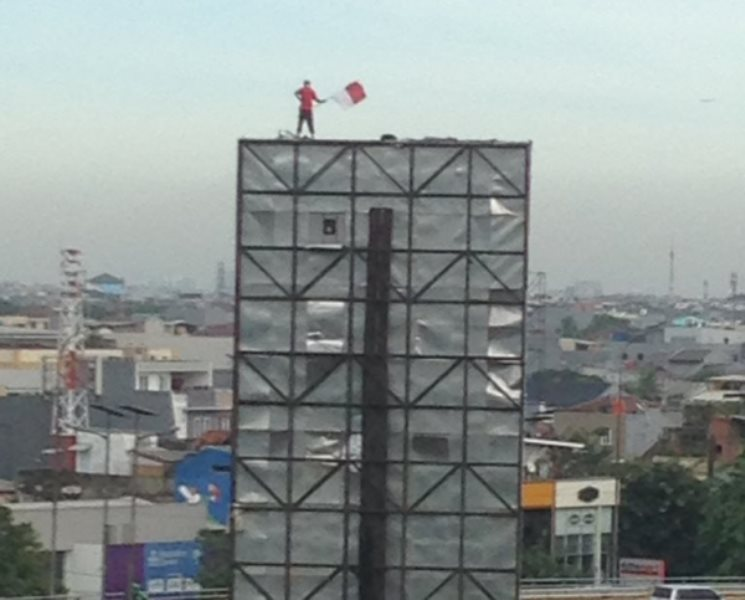 Pira yang berdiri di atas pepan reklame di Grogol. Foto @c_munir