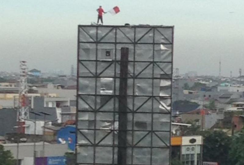 Martinus saat di atas papan reklame (foto: akun Twitter @c_munir)