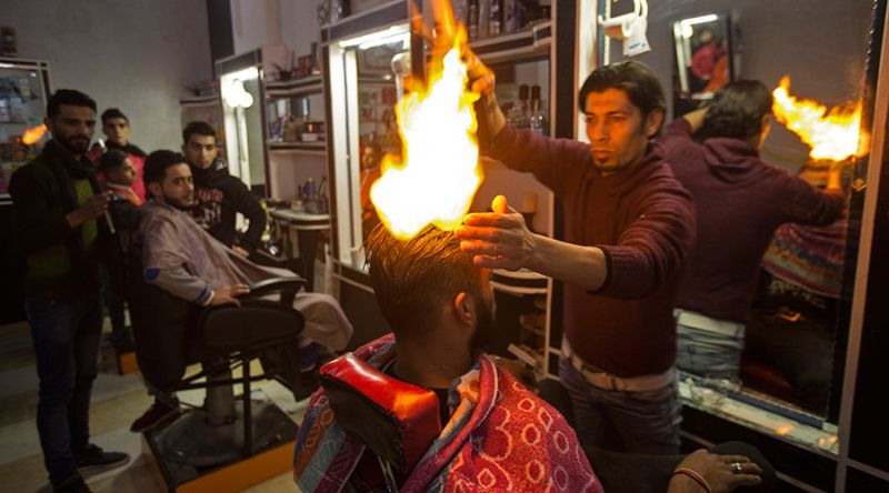 Foto ketika Edwan menata rambut pelanggannya (Foto: AFP)