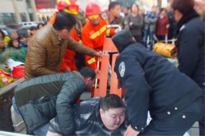 Tandu digunakan untuk membantu mengangkat pria gemuk itu. (Foto: South China Morning Post)