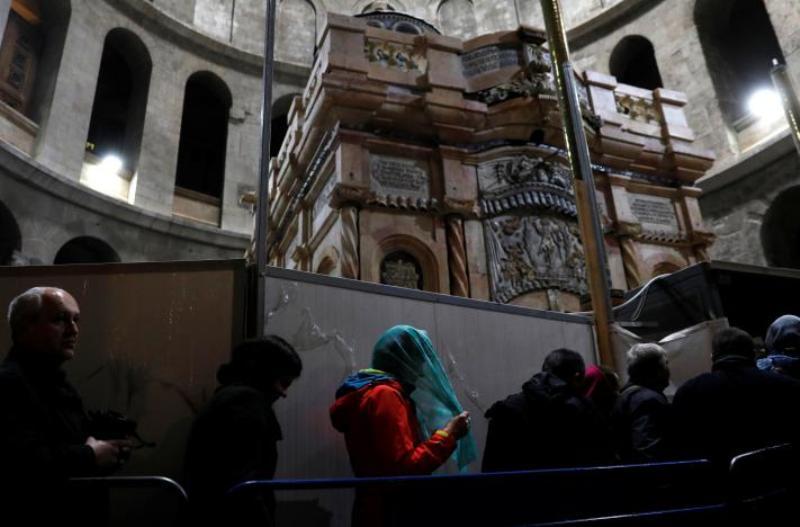 Peziarah berdiri di samping makam Yesus Kristus yang baru selesai diperbaiki (Foto: Ronen Zvulun/Reuters)