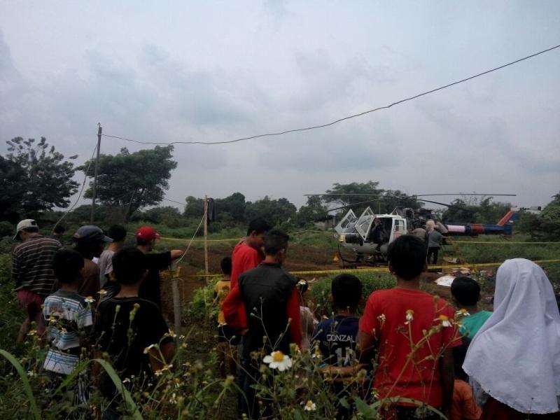 Warga melihat helikopter Polri yang mendarat darurat di kebun warga di Tangerang (Rikhi/Okezone)