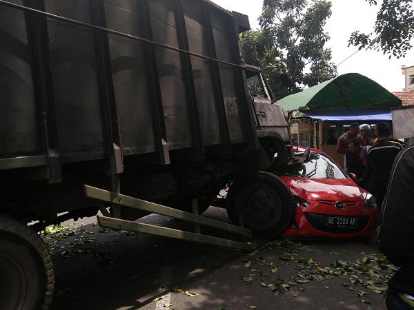Diduga rem blong, truk fuso lompati pembatas jalan hingga tabrak mobil Mazda.