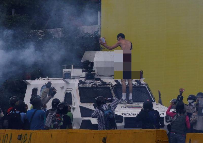Foto ketika pria bugil tersebut naik mobil lapis baja polisi (Foto: Reuters)