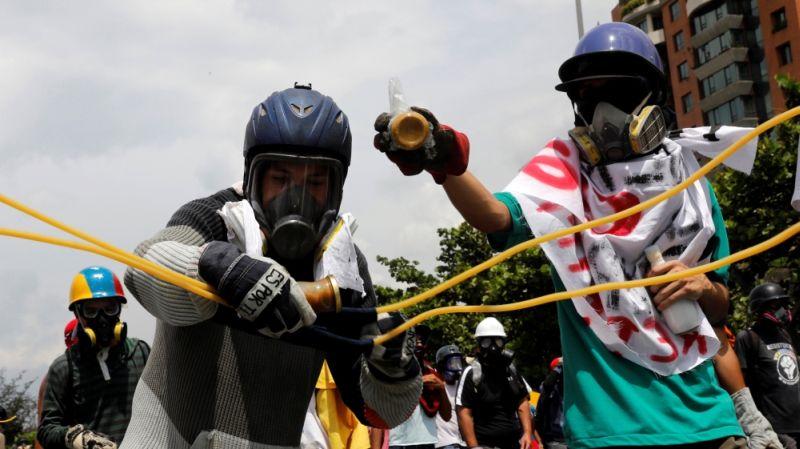 Demonstran yang menggunakan masker melempar botol berisi tinja (Foto: Reuters)