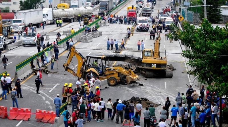 Lubang yang tiba-tiba muncul menelan mobil yang dikendarai ayah dan anak di Meksiko. (Foto: AP)
