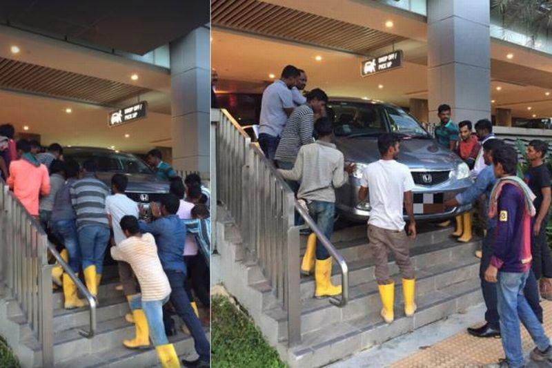 Sekelompok pekerja asing kompak bantu sebuah mobil yang terjebak. (Foto: The Star)