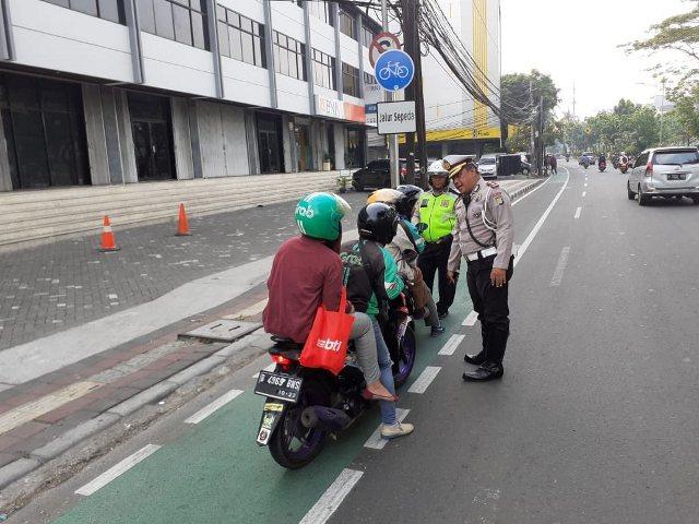 https: img.okezone.com content 2019 11 25 338 2133991 polisi-tilang-pengendara-motor-yang-melintasi-jalur-sepeda-ngNAd5ZaAw.jpg