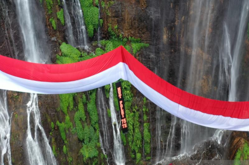 https: img.okezone.com content 2021 07 01 406 2433959 hari-bhayangkara-bendera-merah-putih-raksasa-berkibar-di-wisata-air-terjun-tumpak-sewu-EkysFhXT9K.jpeg