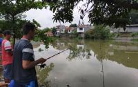 Lapangan Bola Terendam Banjir Jadi Tempat Pemancingan Ikan Dadakan